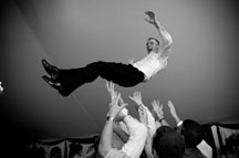 maryland Wedding Photographers captured an image of groom tossed up in the air